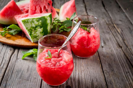 Summer fruit desserts, frozen cocktails. Ice cream granite from watermelon with mint, in portioned glasses, with slices of watermelon. On old rustic wooden table Copy space Imagens - 83741008
