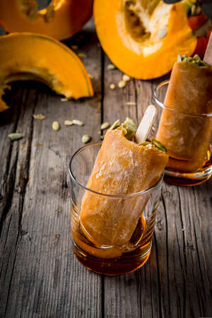 Ideas for autumn dishes from pumpkins. Treats for a Thanksgiving party, Halloween. Pumpkin ice cream popsicles with seeds, in glasses with maple syrup. On wooden old rustic table. Copy space
