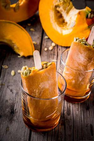 カボチャから秋のお料理のアイデア。感謝祭のパーティー、ハロウィーンのお菓子。種子は、メープル シロップをグラスにカボチャ アイス クリー 写真素材