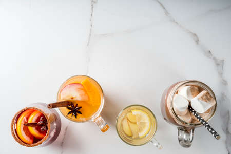 Selection of various autumn traditional drinks: hot chocolate with marshmallow, tea with lemon and ginger, white pumpkin spicy sangria, mulled wine. On white marble table, copy space, top view