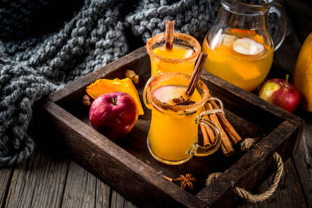Halloween, Thanksgiving. Traditional autumn, winter drinks and cocktails. Spicy hot pumpkin sangria, with apple, cinnamon, anise. In tray, rustic wooden table, glass mugs. Selective focus copy space