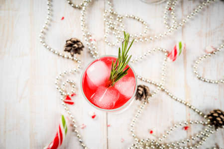 New Years, Christmas drinks. Red alcohol cocktail with cranberry, liqueur, rosemary, with ice. On a white table, with Christmas candies, ornaments and pine cones. Copy space top view