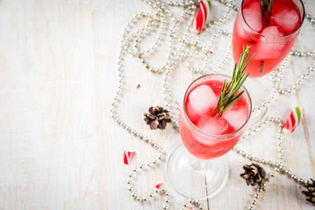 New Years, Christmas drinks. Red alcohol cocktail with cranberry, liqueur, rosemary, with ice. On a white table, with Christmas candies, ornaments and pine cones. Copy space