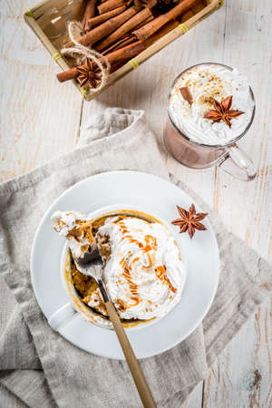 Recipes with pumpkins, fast food, microwave meal. Spicy pumpkin pie in mug, with whipped cream, ice cream, cinnamon, anise. On white wooden table, with cup of hot chocolate. Copy space top view