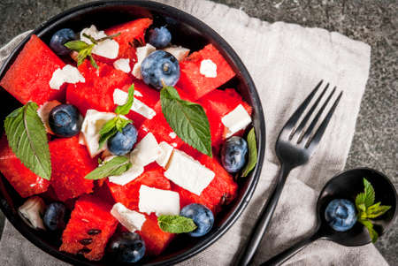 Summer fruit berry salad: watermelon, blueberries, mint, feta cheese and balsamic sauce. On a black bowl, black stone table. With ingredients, fork, knife. Copy space top view Stockfoto