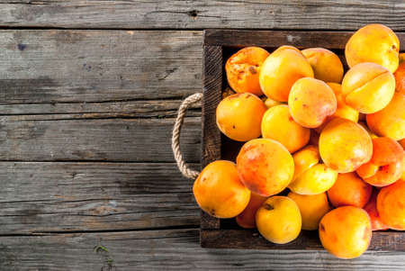 Summer fruits. Fresh raw organic farm apricots in a wooden box, a tray, on an old wooden rustic table. Copy space top view