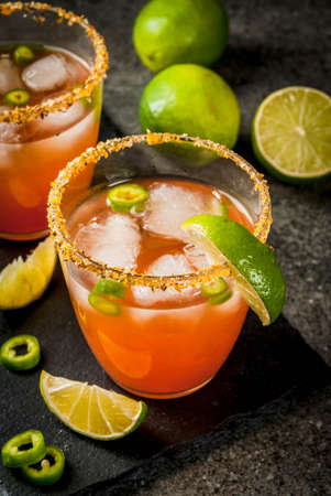 Alcohol. Traditional Mexican South American cocktail. Spicy michelada with hot jalapeno peppers and lime. On a dark stone table. Copy space Stock fotó
