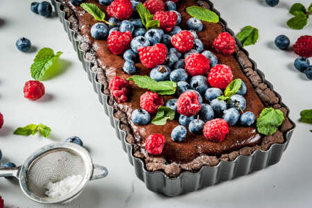 Summer homemade baked pastry. Chocolate cake tart with chocolate cream, fresh raw berries blueberry raspberry, decorated with mint leaves, powdered sugar. On white marble table, copy space