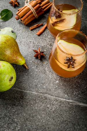 Autumn drinks. Mulled wine. Traditional autumn spicy cocktail with pear, cider and chocolate syrup, with cinnamon, anise, brown sugar. On black stone table. Copy space Stockfoto