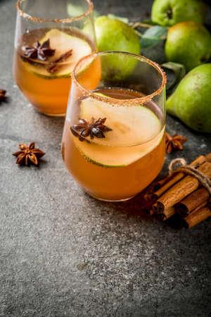 Boissons d'automne. Vin chaud. Cocktail épicé d'automne traditionnel au sirop de poire, de cidre et de chocolat, à la cannelle, aux anis, au sucre brun. Sur la table en pierre noire. Espace de copie Banque d'images
