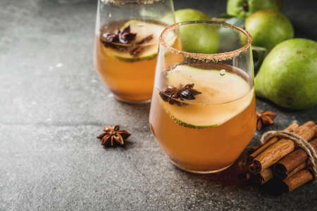 Autumn drinks. Mulled wine. Traditional autumn spicy cocktail with pear, cider and chocolate syrup, with cinnamon, anise, brown sugar. On black stone table. Copy space Banque d'images
