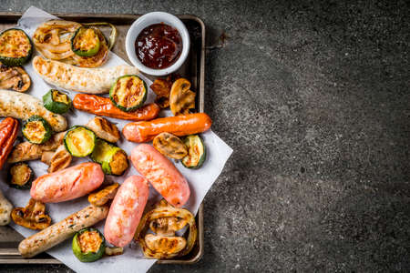 Barbecue. Assortment of various grilled meat sausages, with vegetables BBQ - mushrooms, tomatoes, zucchini, onions. On a black stone table, on a baking sheet, with sauce. Copy space top view Stockfoto