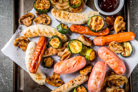 Barbecue. Assortment of various grilled meat sausages, with vegetables BBQ - mushrooms, tomatoes, zucchini, onions. On a black stone table, on a baking sheet, with sauce. Copy space Stockfoto