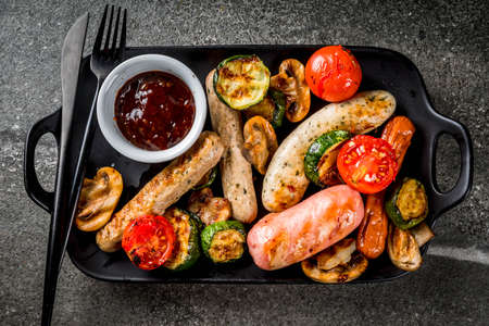 Barbecue. Assortment of various grilled meat sausages, with vegetables BBQ - mushrooms, tomatoes, zucchini, onions. On a black stone table, on a black plate, with sauce. Copy space top view