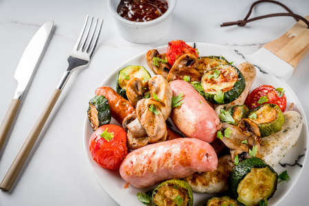 Barbecue. Assortment of various grilled meat sausages, with vegetables BBQ - mushrooms, tomatoes, zucchini, onions. On white marble table, on plate, with sauce. Copy space