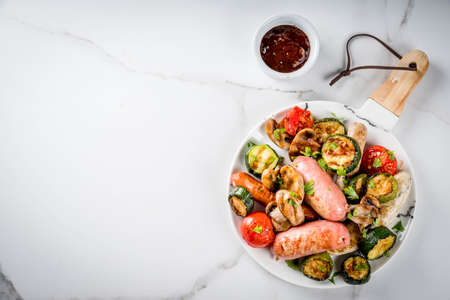 Barbecue. Assortment of various grilled meat sausages, with vegetables BBQ - mushrooms, tomatoes, zucchini, onions. On white marble table, on plate, with sauce. Copy space top view