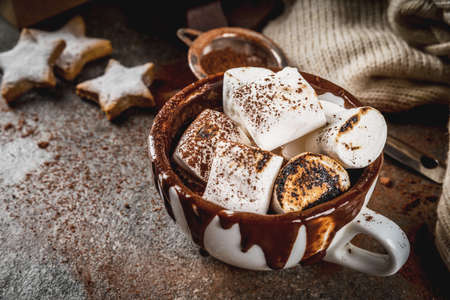 New Year and Christmas treats. Traditional sweets. A cup of hot chocolate with marshmallow fried on fire, gingerbread stars, with sweater on black stone background, copy space Banque d'images