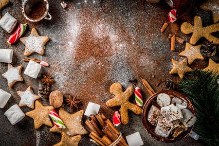 New Year, Christmas treats. Cup of hot chocolate with fried marshmallow, ginger star cookies, gingerbread men, striped candy, spices cinnamon, anise, cocoa, powdered sugar.  Top view copy space frame Stockfoto