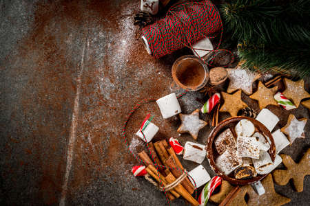 New Year, Christmas treats, sweets. Cup of hot chocolate with fried marshmallow, ginger star cookies, gingerbread men, striped candy, spices cinnamon anise, cocoa, powdered sugar.  Copy space top view Banque d'images