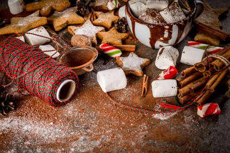 New Year, Christmas treats, sweets. Cup of hot chocolate with fried marshmallow, ginger star cookies, gingerbread men, striped candy, spices cinnamon anise, cocoa, powdered sugar.  Copy space Stockfoto
