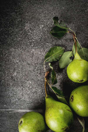 Fresh raw organic farm pear with leaves on a black stone table, copy space top view