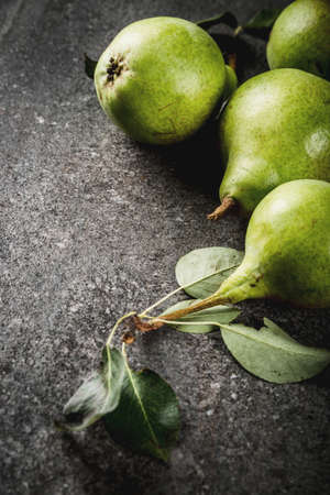 Fresh raw organic farm pear with leaves on a black stone table, copy space