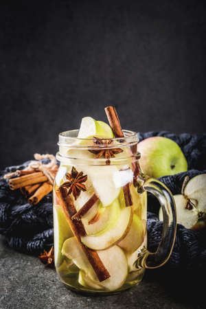 Autumn cocktail. Infused diet detox water with apples and spices - anise, cinnamon. Alcohol cocktail with apple cider. In mason jar on a black stone table. Copy space Banque d'images