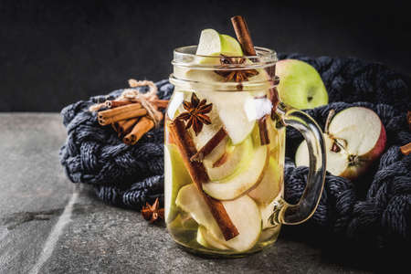Autumn cocktail. Infused diet detox water with apples and spices - anise, cinnamon. Alcohol cocktail with apple cider. In mason jar on a black stone table. Copy space Stockfoto