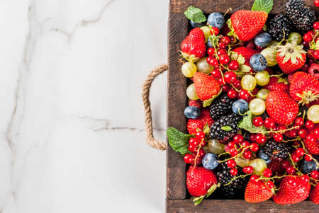 Summer fruit and berries. 6 types of raw organic farmer berries - raspberries blackberries blueberries strawberries red currants gooseberries. White marble table, wooden tray box. Copy space top view Banque d'images
