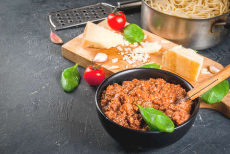 Ingredients of Italian cuisine. Products for the preparation of pasta bolognese, the cooking process. Welded spaghetti in pan, bolognese sauce, basil, garlic, tomato, parmesan Copy space