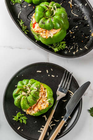 Autumn recipes. Homemade stuffed bell pepper with minced meat, carrots, tomatoes, herbs, cheese. On white marble table, in portioned plate, with knife and fork, Copy space top view