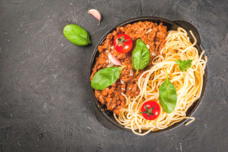 Ingredients of Italian cuisine. Products for the preparation of pasta bolognese, the cooking process. Spaghetti, bolognese sauce, basil, garlic, tomato, parmesan  in pan. Copy space