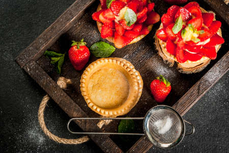 Summer and spring dessert. Home pies tartlets with custard and strawberries, decorated with mint and powdered sugar. On black stone table, rustic, with wooden board, tray. Copy space top view