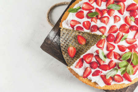 table top: Homemade biscuit cake with whipped cream, fresh organic raw strawberries and mint. On a white stone table. Copy space top view