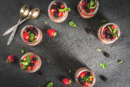Healthy vegan breakfast. Dessert. Alternative food. Pudding with chia seeds, fresh strawberries, blackberries and mint. On a dark stone background. Copy space top view