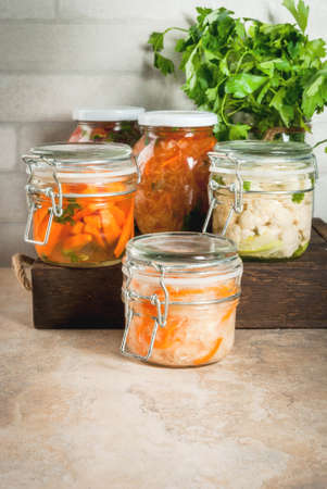 Concept of a fermented meal. Home canned food and billets. Vegan food. Vegetables. Cans of canned salsa, sauerkraut, marinated carrots, kimchi and cauliflower broccoli. Home kitchen table. copy space Banque d'images