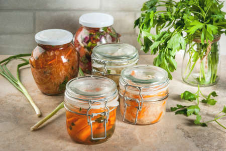 Concept of a fermented meal. Home canned food and billets. Vegan food. Vegetables. Cans of canned salsa, sauerkraut, marinated carrots, kimchi and cauliflower broccoli. Home kitchen table. copy space Stockfoto