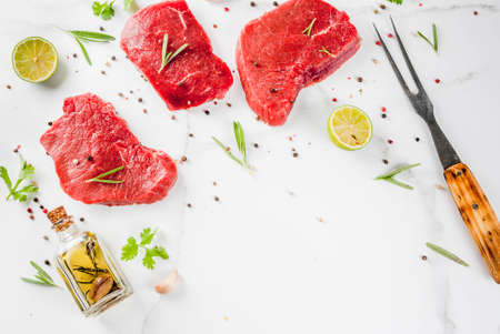 table top: Fresh raw meat. Beef tenderloin, steaks, on a white marble table. With olive oil, spices for cooking - basil, rosemary, coriander, parsley, garlic, lemon, salt, pepper. Top view copy space Stock Photo