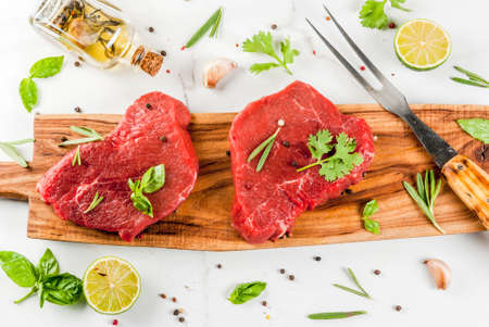 Fresh raw meat. Beef tenderloin, steaks, on a white marble table. With olive oil, spices for cooking - basil, rosemary, coriander, parsley, garlic, lemon, salt, pepper. Copy space top view Banque d'images