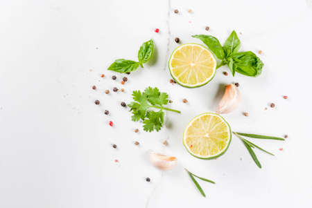 Food cooking background, white marble kitchen table. Spices and herbs for cooking dinner - coriander, parsley, basil, rosemary, lime, tomato, salt, pepper, garlic. Copy space top view