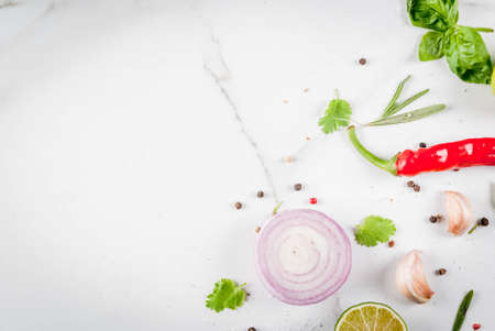 Food cooking background, white marble table. Spices, herbs for dinner - coriander, parsley, basil, rosemary, lime, tomato, salt, pepper, garlic, onion, tomato, red chili pepper. Copy space top view