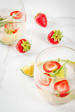 Summer refreshing cocktail. Lemonade with lime, fresh strawberries and rosemary. On a white marble table. Copy space
