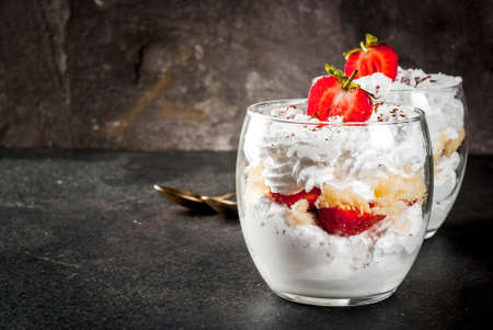 Layered dessert parfait in a glass with strawberries, sponge cake and whipped cream. On a black stone table. Copy space Banque d'images