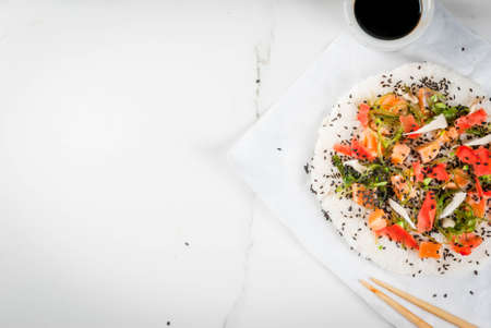 Trend hybrid food. Japanese, Asian cuisine. Sushi pizza with salmon, hayashi wakame, daikon, pickled ginger, red caviar. On a white marble table, with chopsticks and soy sauce. Copy space top view Stock Photo