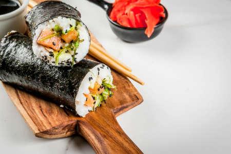 Trend hybride voedsel. Japanse, Aziatische keuken. Sushi-burrito, sandwich met zalm, hayashi wakame, daikon, gepekelde gember, rode kaviaar. Op een witmarmeren tafel, met stokjes en sojasaus. Ruimte kopiëren