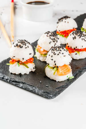 Trend hybrid food. Japanese Asian cuisine. Mini sushi-burgers, sandwiches with salmon, hayashi wakame, daikon, ginger, red caviar. White marble table, with chopsticks, soy sauce. Copy space Stock Photo