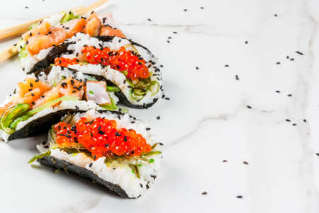 Trend hybrid food. Japanese Asian cuisine. Mini sushi-tacos, sandwiches with salmon, hayashi wakame, daikon, ginger, red caviar. White marble table, with chopsticks, soy sauce. Copy space Stock Photo