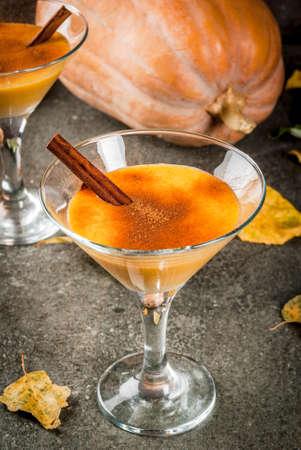 秋と冬のドリンク。感謝祭、ハロウィン カクテル。黒い石のテーブルに、シナモンスティック パンプキンパイ マルガリータ。紅葉、格子縞、カボ