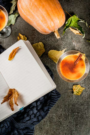 Fall and winter drinks. Thanksgiving and Halloween cocktails. Pumpkin pie margarita with cinnamon stick, on black stone table. Cozy home, with autumn leaves, plaid, pumpkin, book, copy space top view