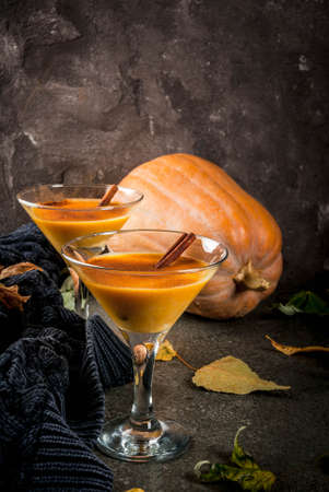 Fall and winter drinks. Thanksgiving and Halloween cocktails. Pumpkin pie margarita with cinnamon stick, on black stone table. Cozy home, with autumn leaves, plaid, pumpkin, copy space